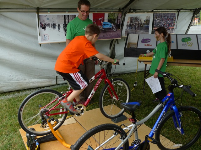 Dr. Keith MacCormick encouraging youth on a pedal power generator bike